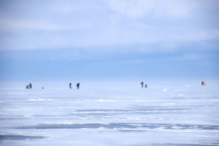People on frozen lake against sky during foggy weather