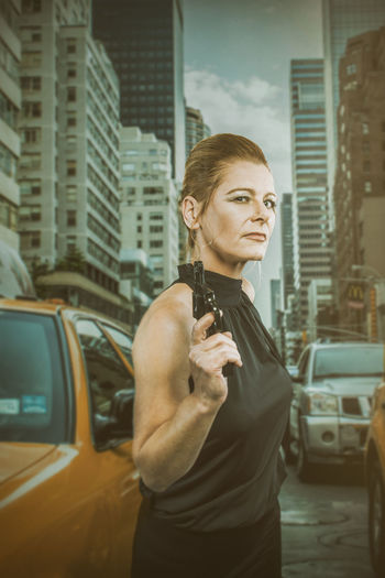 Portrait Of Woman Holding Gun While Standing On City Street