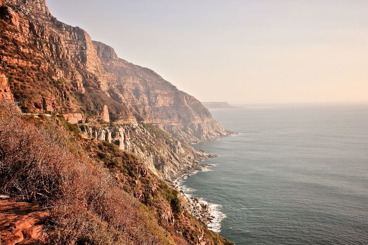 Scenic view of chapmans peak drive by sea against clear sky