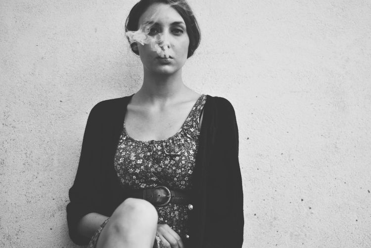 Close-up portrait of young woman exhaling smoke against wall