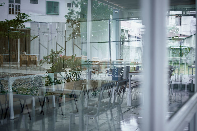 Empty chairs and tables by glass window in rainy season
