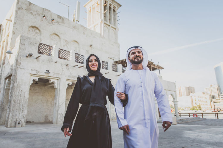 Low angle view of smiling couple walking on street in town