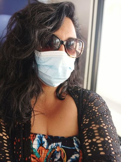 Portrait of carefree woman wearing sunglasses and protective face mask while sitting by window