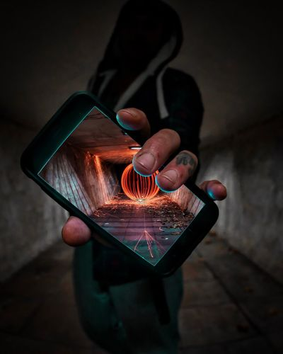 Man showing wire wool on smart phone screen in tunnel