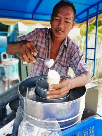 Vendor making ice cream cone at market
