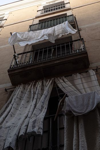 Low angle view of clothes drying on balcony of building