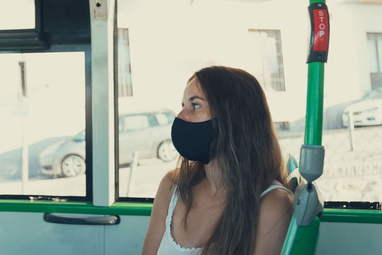 Girl with a mask traveling on the city bus