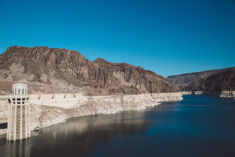 Hoover dam by colorado river against clear blue sky