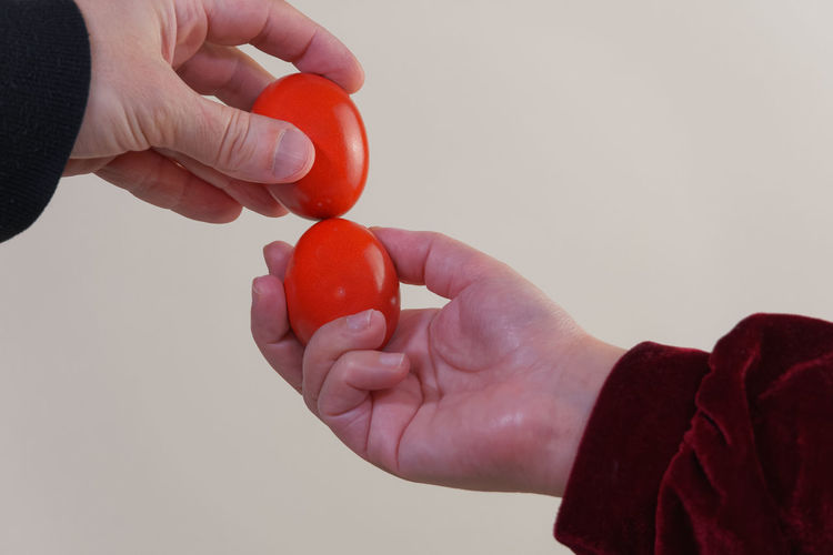 Cropped hands of people holding red eggs against white background