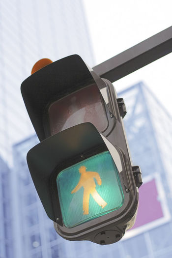Traffic light in a city City Cityscape Downtown Pedestrian Crossing Close-up Crossroad Focus On Foreground Green Light Guidance Human Representation Illuminated Light Lighting Equipment Low Angle View Pedestrian Road Sign Road Signal Safety Sign Stoplight Traffic Light  Transportation