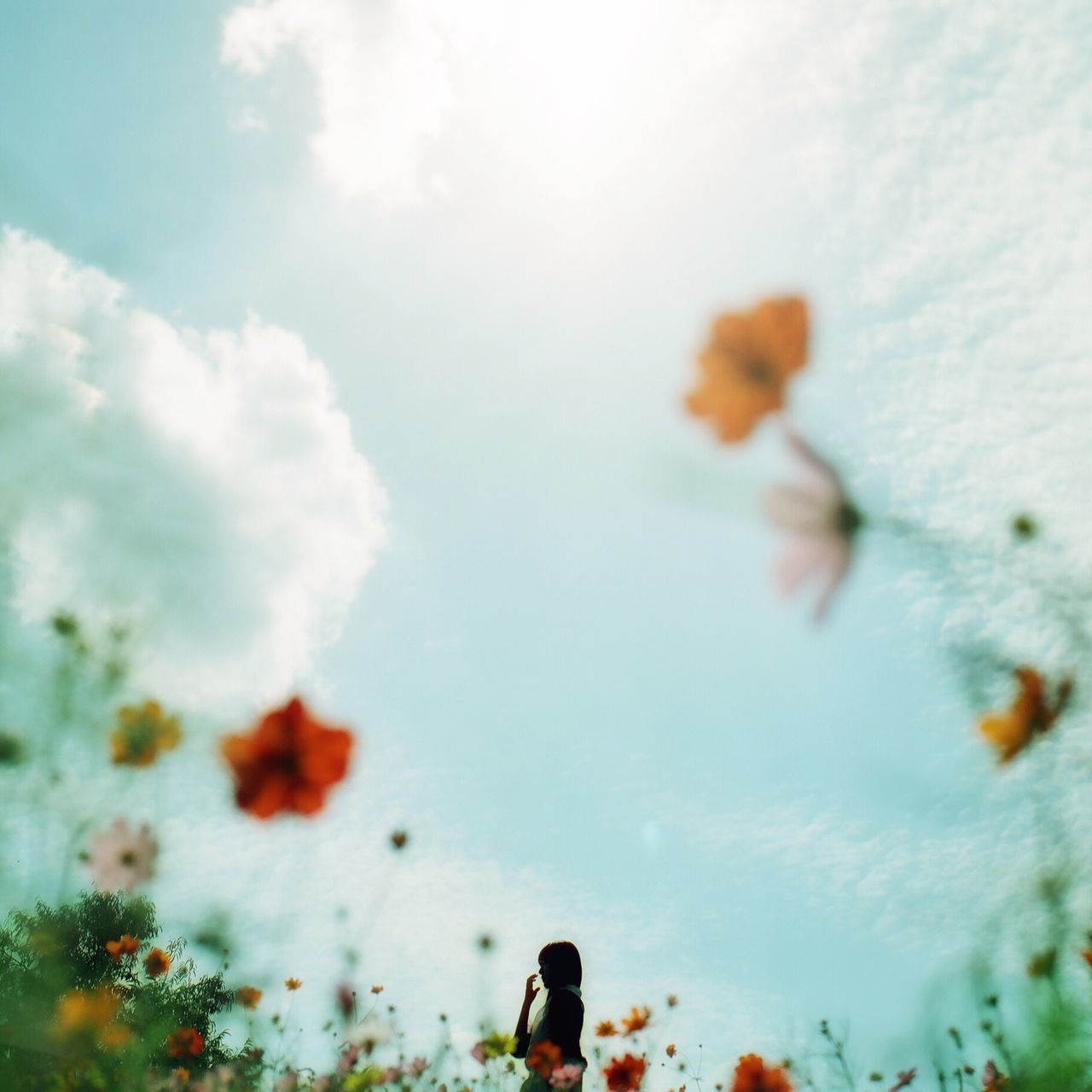 Low angle view of woman on field against cloudy sky