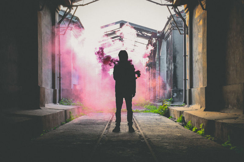 Full Length Of Silhouette Person Standing By Abandoned Building With Pink Smoke In Background
