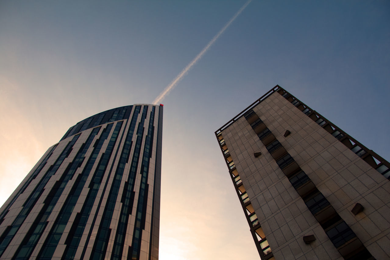 architecture, low angle view, built structure, building exterior, skyscraper, no people, outdoors, day, city, sky, modern, sunset, vapor trail