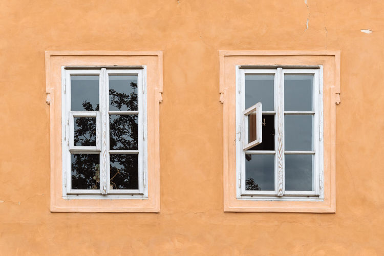 Two old windows in orange color wall Bohemia City Czech Republic Architecture Building Building Exterior Built Structure Closed Day Full Frame Glass Glass - Material House Low Angle View No People Outdoors Protection Residential District Security Transparent Two Wall Wall - Building Feature Window Window Frame