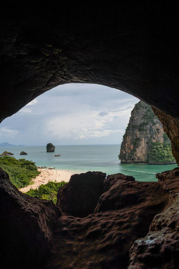 Lime Stone Formations and Beach seen from a Cave, Phra Nang, Railay Beach, Krabi, Thailand Ao Nang, Krabi. Krabi Railay Thailand Tourist Tourist Attraction  Travel Beach Beauty In Nature Cliff Day Destination Horizon Over Water Limestone Nature No People Ocean Outdoors Railay Beach Rock - Object Rock Formation Scenics Sea Sky Southeastasia Tourism Tourist Destination Tranquil Scene Tranquility Travel Destinations Tree Water