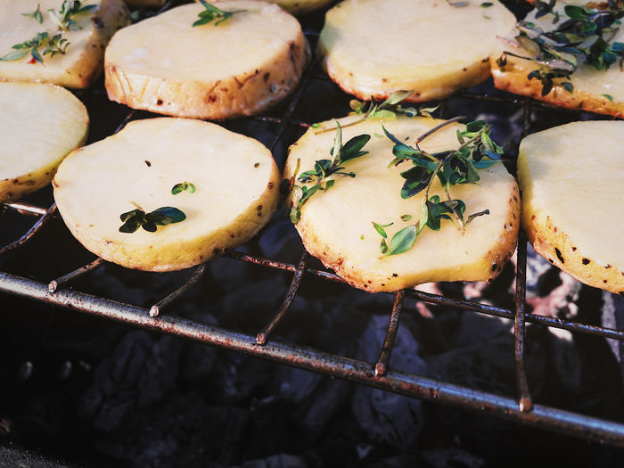 Grilling fresh potatoes. Barbecue Close-up Food Freshness Grilled Grilled Potatoes Healthy Eating Healthy Food Herbs High Angle View No People Outdoors Potatoes Preparation  Sliced Potatoes