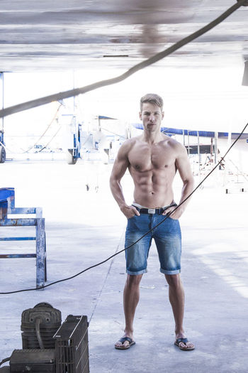 Full length portrait of shirtless man standing outdoors
