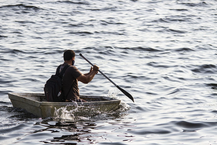 Rear view of man wearing mask sitting on boat in lake