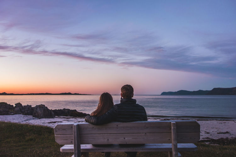 Rear View Of Couple Sitting On Shore Against Sky During Sunset