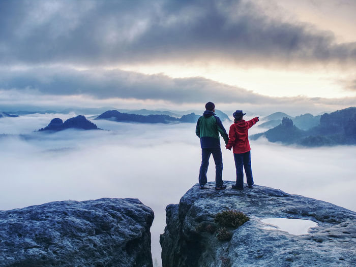 Lovers mirroring in water eye at mountain summit above thick mist. climbing for mazing aerial view