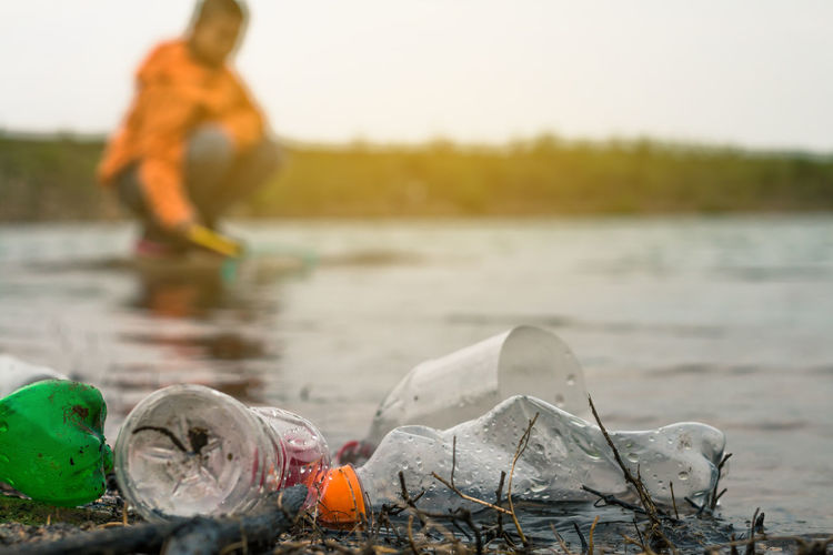 Close-up of plastic bottles at lakeshore with boy crouching in background