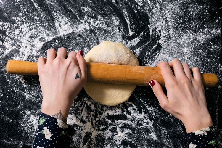 Cropped hands of woman rolling dough in kitchen