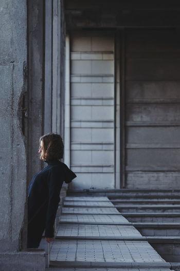 Side view of woman standing by columns below bridge
