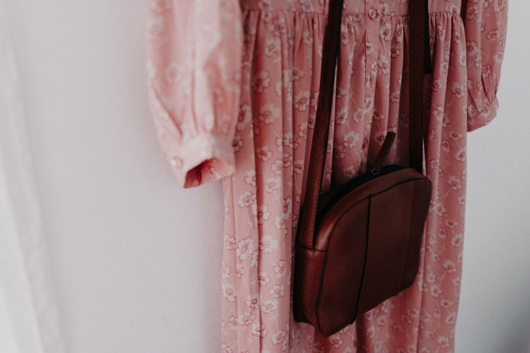High angle view of bag with dress hanging on wall