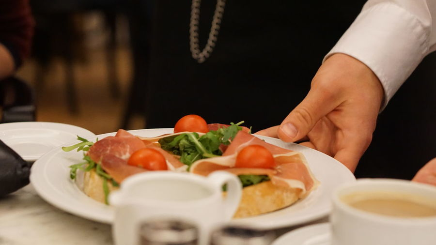 Midsection of person serving food on table