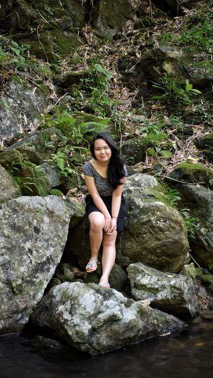 Portrait of smiling woman sitting on rocks