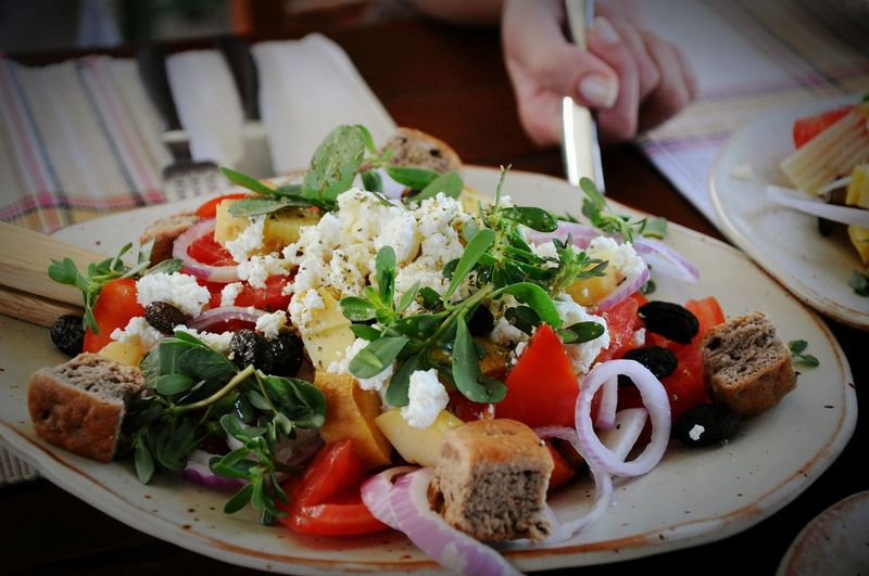 Close-up of fresh greek salad served in plate on table at restaurant