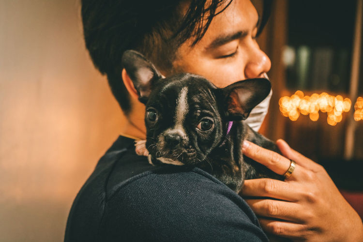 Close-up of man holding puppy