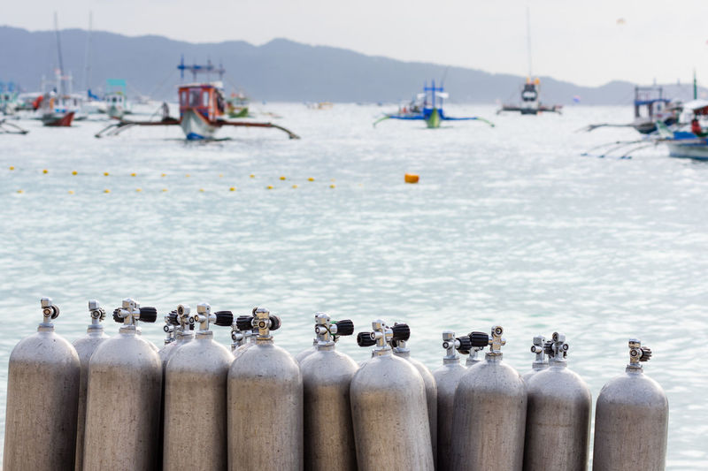 A collection of scuba divers air tanks on a tropical white sand beach with depth of field back ground of calm sea and pump boats. Philippines Scuba Diving Tanks Day Diving Lesson Diving School Diving Tanks Focus On Foreground In A Row Outdoors Oxygen Tank Paradise Beach Pressurized Scuba Tank Sea Water