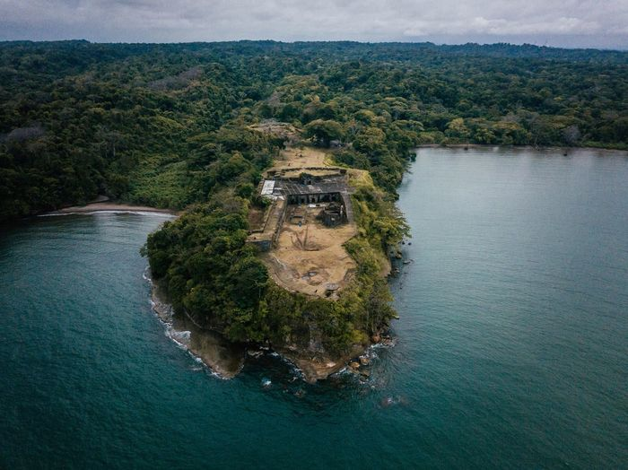 High angle view of abandoned building on cliff amidst sea