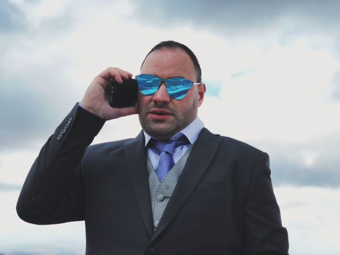 Portrait of businessman in sunglasses talking on mobile phone against sky