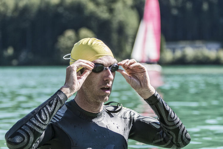 Male triathlete wearing goggles in river