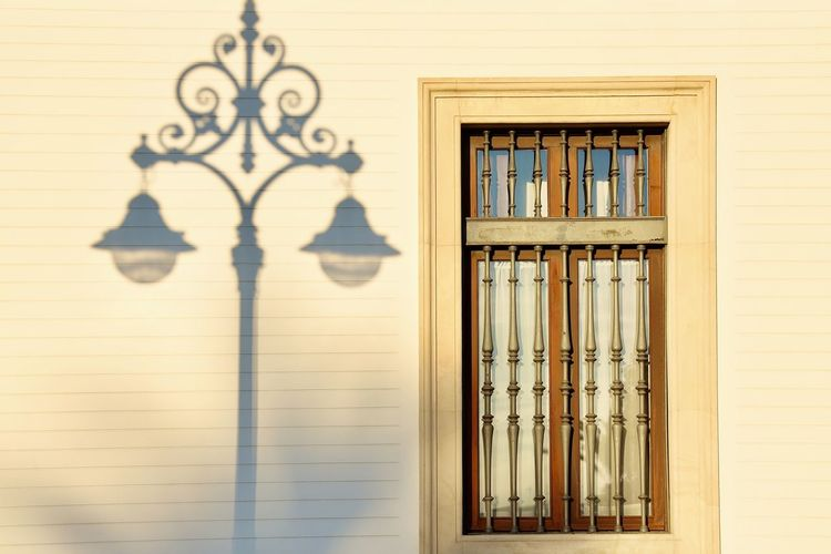 Close-up of window in building with a shadow of a street lamp