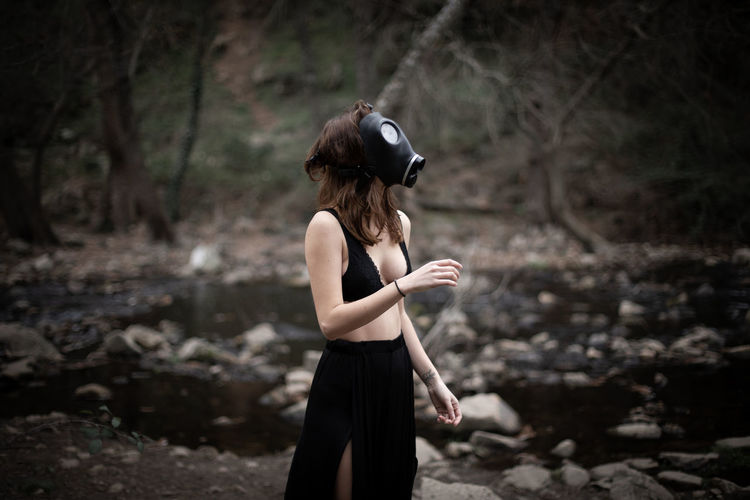 Side view of sensuous woman wearing gas mask while standing in forest