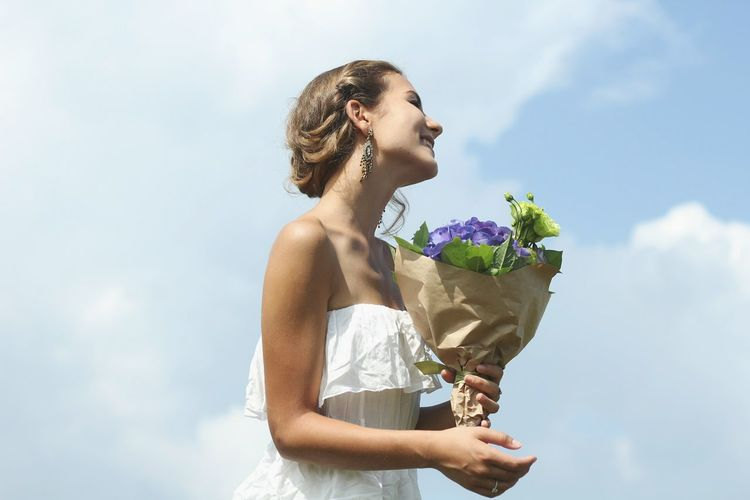 Young woman holding bouquet against sky
