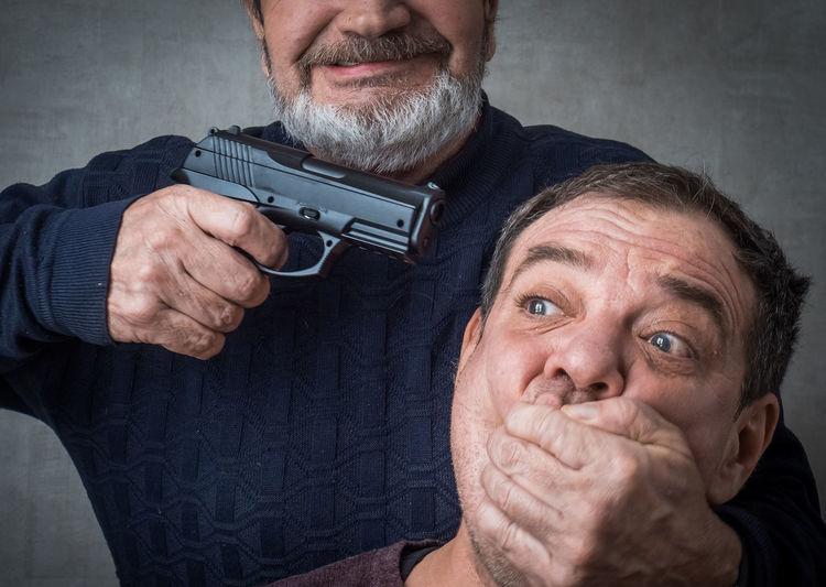 Senior man aiming gun while covering victims mouth