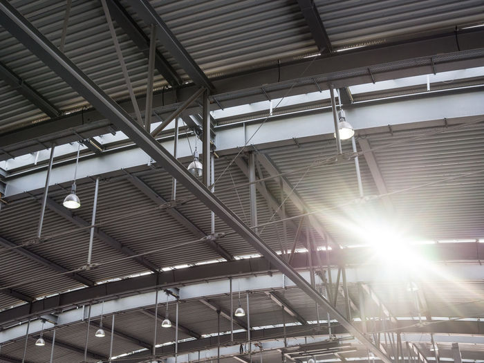 Low angle view of sun shining through roof of train station