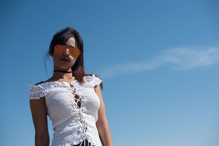 Low angle view of fashionable woman standing against blue sky