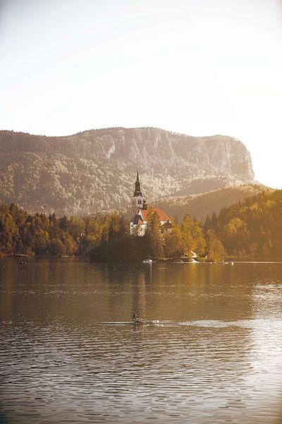 Solitude Slovenia Lake Bled Water Sky Nature Mountain Lake Building Exterior Waterfront Architecture Day Clear Sky Tree Beauty In Nature Plant Outdoors One Person Built Structure Scenics - Nature Men Lifestyles