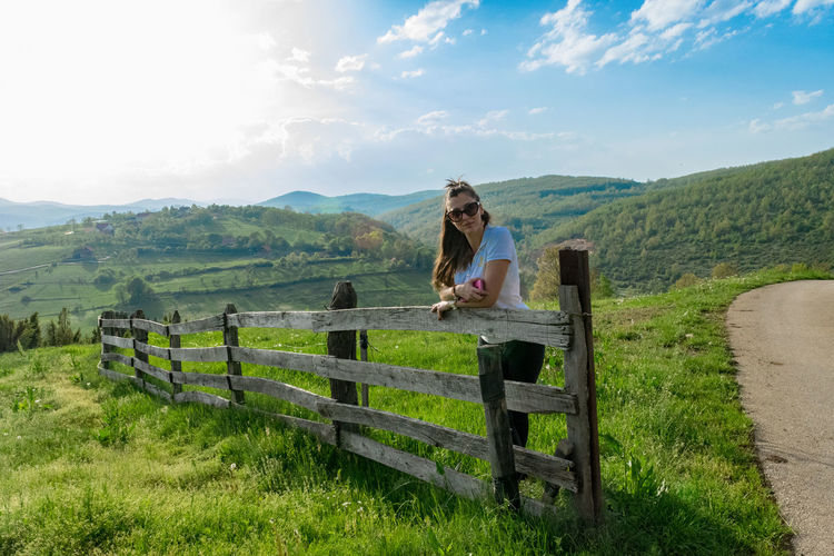 Barrier Beauty In Nature Boundary Casual Clothing Day Environment Fence Field Full Length Grass Land Landscape Mountain Range Nature Non-urban Scene One Person Outdoors Plant Rural Scene Scenics - Nature Sky Tranquility
