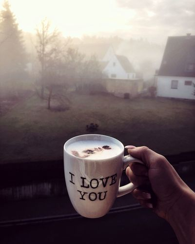 Close-up of hand holding coffee cup against foggy weather