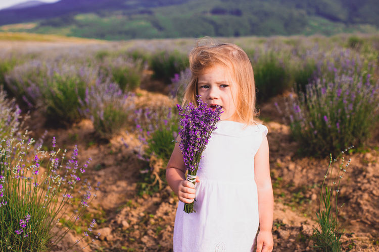 Portrait of cute girl holding flowers while standing outdoors