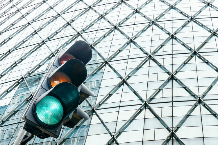 Low angle view of traffic lights against glass building in the city