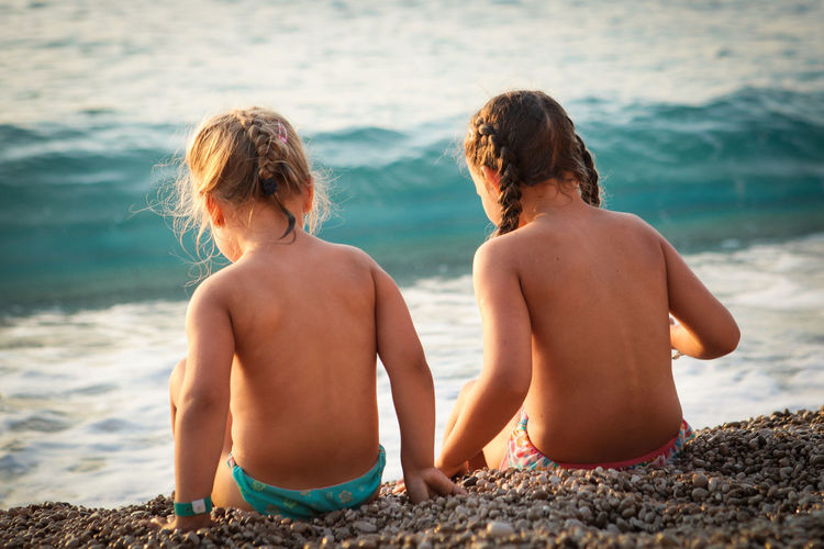 Two girls sitting on a pebble beach during sunset Sunset Pebble Females Girls Couple - Relationship Outdoors Positive Emotion Child Leisure Activity Childhood People Land Bonding Family Sitting Beach Nature Shirtless Sea Rear View Togetherness Water Two People Summer Vacation Holiday