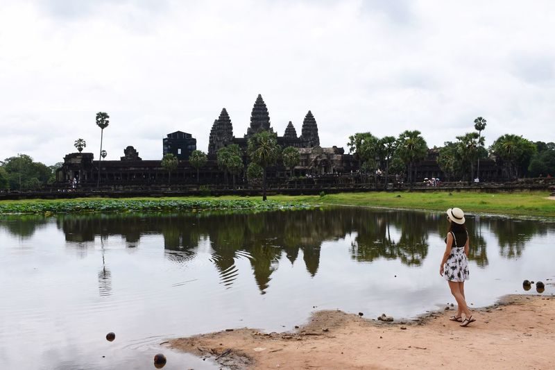 Rear View Of Woman Standing By Lake At Angkor Wat Against Sky