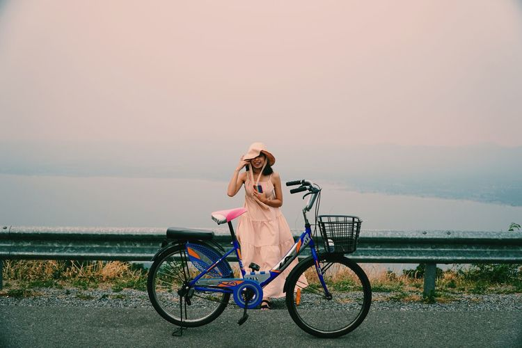 Woman standing by bicycle against sky